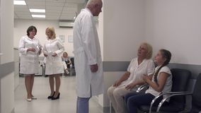 In the hall of the hospital. Visitors to the medical center are waiting for a doctor. Two nurses communicate in the hall of the hospital. The doctor comes to the stock footage