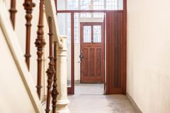 Hall ingång i ett gammalt hus med en trädörr och trappa royaltyfria bilder