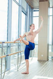In the hall man doing stretching near Barre Royalty Free Stock Images