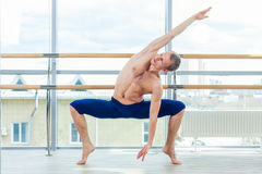In the hall man doing stretching near Barre Royalty Free Stock Image
