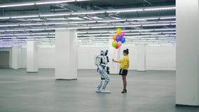 Hall massif avec un robot obtenant des ballons d'une dame banque de vidéos