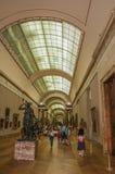 Hall med besökare och konstverk på Louvremuseet i Paris royaltyfria bilder