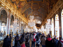 Hall of mirrors in the palace of Versailles. Many people are visiting the famous Hall of Mirrors (French: Grande Galerie or Galerie des Glaces) which is the Royalty Free Stock Photography