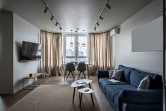 Hall in modern style. Stylish modern interior with white walls and a parquet with a carpet on the floor. There is a blue sofa with pillows, wooden tables, chairs Stock Photos