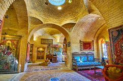 The hall of old rug bazaar, Shiraz, Iran. SHIRAZ, IRAN - OCTOBER 14, 2017: The scenic brick hall of traditional carpet store with a dome, light hole, vintage royalty free stock photo