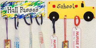 Hall passes. A row of hall passes hanging on the wall of a school room Stock Photo