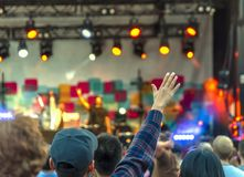 Hall at the pop concert, the viewer`s hand, raised up, blurred stock photography