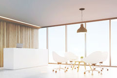 Hall with wooden walls, large panoramic window a black ceiling lamp hanging above a coffee table surrounded by white office chairs Royalty Free Stock Photo