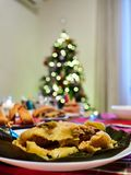 Hallaca served with jam bread with christmas tree at the background. Hallaca is a typical Venezuelan food served during holidays. Festivities stock photo