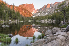 Hallett Peak Alpenglow. The first reddish light of alpenglow hits Hallett Peak, reflected in Dream Lake in Rocky Mountain National Park, Colorado Stock Photos