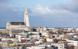 Hallgrimskirkja church under sky, Iceland. Cityscape of Reykjavik, capital city of Iceland. Modern buildings and Hallgrimskirkja church under cloudy sky Royalty Free Stock Images