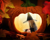 Hallloween Witch Reading Book In Pumpkin. A little halloween witch is sitting inside a glowing pumpkin reading a story book with magical sparkles for a mystery stock photography