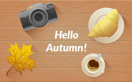 Hallo autumn text. Tasty buttery croissant and cup and camera of hot coffee. On old wooden table with yellow leaves. Flat vector illustration Stock Images