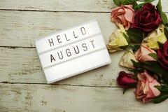 Hallo blühen August Word auf Leuchtkasten mit Rosen Blumenstrauß auf hölzernem Hintergrund stockfotografie