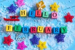 Hallo Februar geschrieben auf Farbhölzerne Spielzeugwürfel auf hellem Hintergrund mit Schnee Lizenzfreies Stockbild