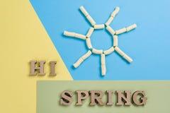 Hallo Frühling, abstraktes Bild mit hölzernen Buchstaben auf dem Hintergrund der Sonne und blaues Gelbgrün Stockfotos