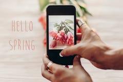 Hallo Frühlingstextzeichen, Hand, die das Telefon macht Foto von Griffeln hält lizenzfreies stockbild