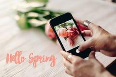 Hallo Frühlingstextzeichen, Hand, die das Telefon macht Foto von Griffeln hält Stockbild