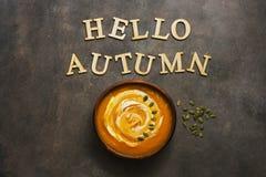 Hallo Herbst - warme Kürbiscremesuppe mit Sahne und Samen auf einem braunen rustikalen Hintergrund r obenliegend lizenzfreies stockfoto