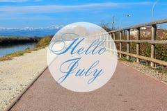 Hallo Juli-Grußkarte mit Sommerhinterweghintergrund lizenzfreies stockbild