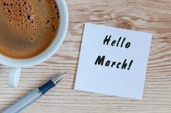 Hallo MÄRZ - Anmerkung am hölzernen Bürotisch mit Stift und am Becher Morgenkaffee junge gelbe Blume gegen weißen Hintergrund Stockbilder
