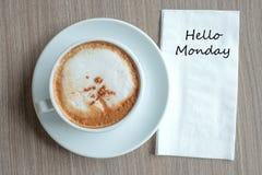 Hallo Montag-Text auf Papier mit heißer CappuccinoKaffeetasse auf Tabellenhintergrund am Morgen lizenzfreie stockbilder