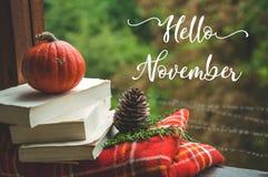 Hallo November Gemütliches Herbststillleben: höhlen Sie und öffnete Buch auf Weinlesefensterbrett mit roter Decke, Kürbis, Kerzen stockbilder