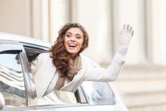 Hallo! Schöne junge Frau, die heraus von einem Guten Tag sagenden Auto schaut lizenzfreie stockfotos