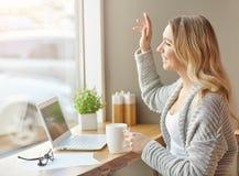 Hallo Schöne junge Frau, die mit Computer arbeitet, eine Schale des Getränks hält und in das Fenster wellenartig bewegt Lizenzfreies Stockbild