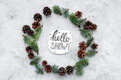 Hallo Schneehandbeschriftung Wintermuster mit Fichtenzweig und Kegel auf Draufsicht des grauen Hintergrundes Stockfotos