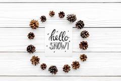 Hallo Schneehandbeschriftung Wintermuster mit pinecones auf weißem hölzernem copyspace Draufsicht des Hintergrundes Lizenzfreie Stockfotografie