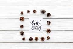 Hallo Schneehandbeschriftung Wintermuster mit pinecones auf weißem hölzernem copyspace Draufsicht des Hintergrundes Lizenzfreie Stockfotos