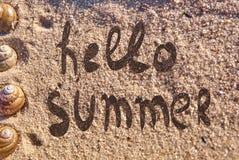 Hallo Sommertext gezeichnet auf einen Sand stockbilder