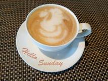 Hallo Sonntags-Grüße mit einem weißen Tasse Kaffee und natürlichen einem Mattenmusterhintergrund lizenzfreies stockbild