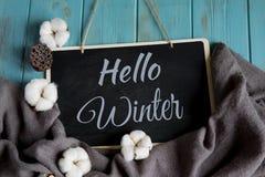 Hallo Winterpostkarte Winterfahne mit warmem grauem Schal, Baumwollblumen auf einem blauen hölzernen Hintergrund stockfotografie