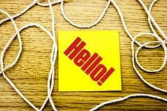 Hallo - Wort auf gelber klebriger Anmerkung im hölzernen Hintergrund Geschäftskonzept lizenzfreie stockfotografie