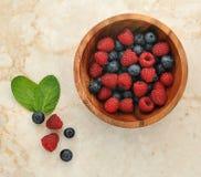 Hallon och blåbär i en träbunke Fotografering för Bildbyråer