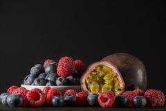 Hallon och blåbär med en passionfruit, på mörk bakgrund, Fotografering för Bildbyråer