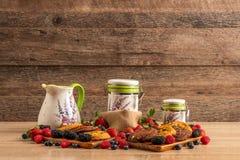 Hallon, skogfrukter och chokladsconeser på träuppläggningsfatet fotografering för bildbyråer