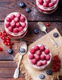 Hallonefterrätten, ostkaka, förspiller tiden, musen i ett exponeringsglas på en träbakgrund Top beskådar Royaltyfri Foto