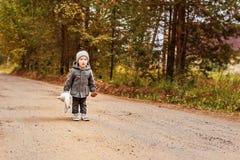 Halloo gritador del muchacho perdido del niño en el bosque en una capa gris con un conejito del juguete y una seta en sus manos imagen de archivo
