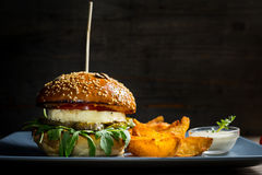 Halloumi burger. Closeup of Halloumi burger with fries on plate Stock Images