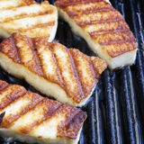 Grilling Halloumi Cheese. Halloumi cheese frying in grill pan Royalty Free Stock Images