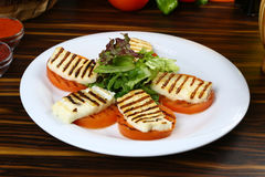 Halloumi cheese. Frying grill on tomatoes Royalty Free Stock Images