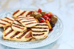 Halloumi cheese. Grilled halloumi cheese with olives and pepers Royalty Free Stock Image