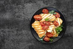 Halloumi Cheese with Roasted Cherry Tomatoes and Herbs. Halloumi cheese, grilled, with roasted cherry tomates and herbs. Top view over dark slate Stock Image