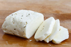 Halloumi cheese. Sliced halloumi cheese with mint on wooden board in perspective Stock Photos