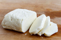 Halloumi cheese. Sliced halloumi cheese on wooden board in perspective Stock Photo