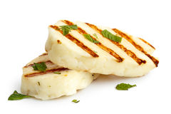 Halloumi cheese. Two grilled slices of halloumi cheese isolated on white in perspective. With grill marks and mint Stock Photography