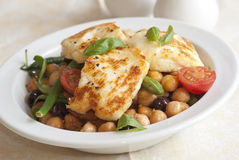 Halloumi salad. Delicious salad with Halloumi cheese, chickpeas, green beans, tomatoes and olives Royalty Free Stock Image